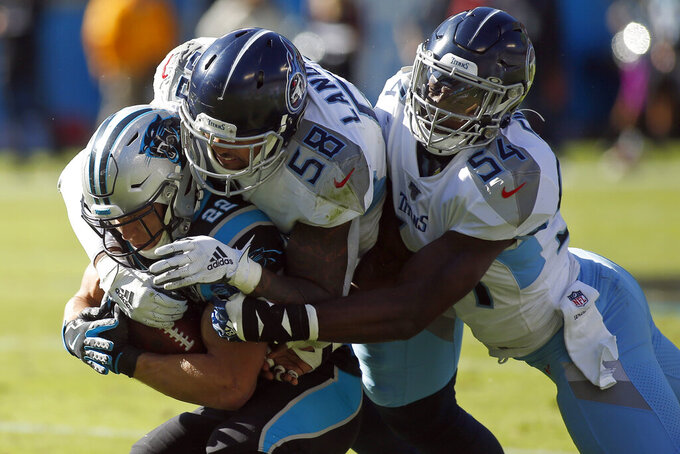 Tennessee Titans inside linebacker Rashaan Evans (54) and linebacker Harold Landry (58) tackle Carolina Panthers running back Christian McCaffrey (22) during the first half of an NFL football game in Charlotte, N.C., Sunday, Nov. 3, 2019. (AP Photo/Brian Blanco)