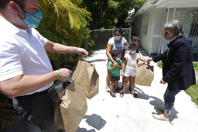 Miami Lighthouse for the Blind and Visually Impaired director of children's programs Isabel Chica, right, and Cameron Sisser, left, vice president for external relations, bring donated food to Greyla Javier, center, and her family, Thursday, Aug. 6, 2020, at Javier's home in Miami. Miami Lighthouse provided the meals to needy families with blind or visually impaired children like Javier's, who have been economically affected by the COVID-19 pandemic. Miami Lighthouse started the Family Security Fund Campaign and has been spending an average of $3,500 a week to help numerous local families who are experiencing food insecurities. (AP Photo/Wilfredo Lee)