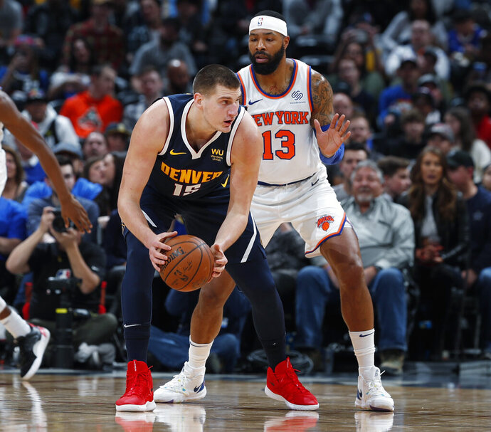 Denver Nuggets center Nikola Jokic, left, looks to pass the ball as New York Knicks forward Marcus Morris Sr. defends in the first half of an NBA basketball game Sunday, Dec. 15, 2019, in Denver. (AP Photo/David Zalubowski)