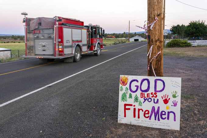 A firetruck responding to the Bootleg Fire is driven past a hand-painted sign thanking firefighters on Wednesday, July 21, 2021 in Bly, Ore. (AP Photo/Nathan Howard)