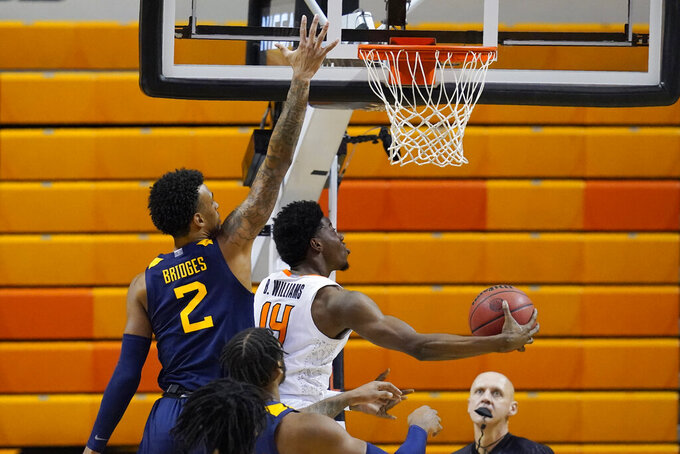 Oklahoma State guard Bryce Williams (14) goes to the basket in front of West Virginia forward Jalen Bridges (2) in the first half of an NCAA college basketball game Monday, Jan. 4, 2021, in Stillwater, Okla. (AP Photo/Sue Ogrocki)
