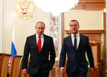 Russian President Vladimir Putin, left, and Russian Prime Minister Dmitry Medvedev walk prior to a cabinet meeting in Moscow, Russia, Wednesday, Jan. 15, 2020. The Tass news agency reports Wednesday that Russian Prime Minister Dmitry Medvedev submitted his resignation to President Vladimir Putin. Russian news agencies said Putin thanked Medvedev for his service but noted that the prime minister's Cabinet failed to fulfil all the objectives set for it. (Dmitry Astakhov, Sputnik, Government Pool Photo via AP)