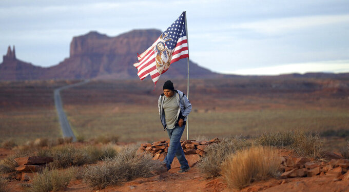 """FILE - In this Thursday, Oct. 25, 2018, photo, Brandon Nez displays his flag at near his jewelry stand in Monument Valley, Utah, where tourists stand the highway to recreate a famous running scene from the movie """"Forest Gump"""". As Native American tribes around the country fight for increased access to the ballot box, Navajo voters in one Utah county could tip the balance of power in the first general election since a federal judge ordered overturned their voting districts as illegally drawn to minimize native voices. Native Americans weren't granted U.S. citizenship until 1924, and even then some states prohibited them from voting for decades if they lived on reservations or couldn't pass an English literacy test. (AP Photo/Rick Bowmer, File)"""