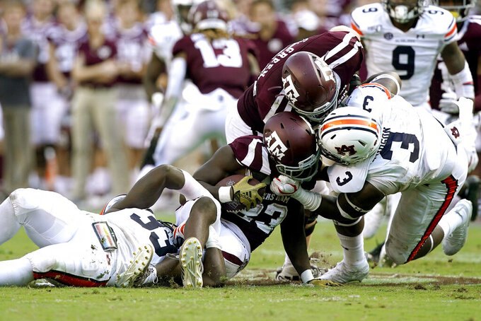 Auburn linebacker K.J. Britt (33) and defensive end Marlon Davidson (3) tackle Texas A&M running back Jacob Kibodi (23) during the third quarter of an NCAA college football game, Saturday, Sept. 21, 2019, in College Station, Texas. (AP Photo/Sam Craft)