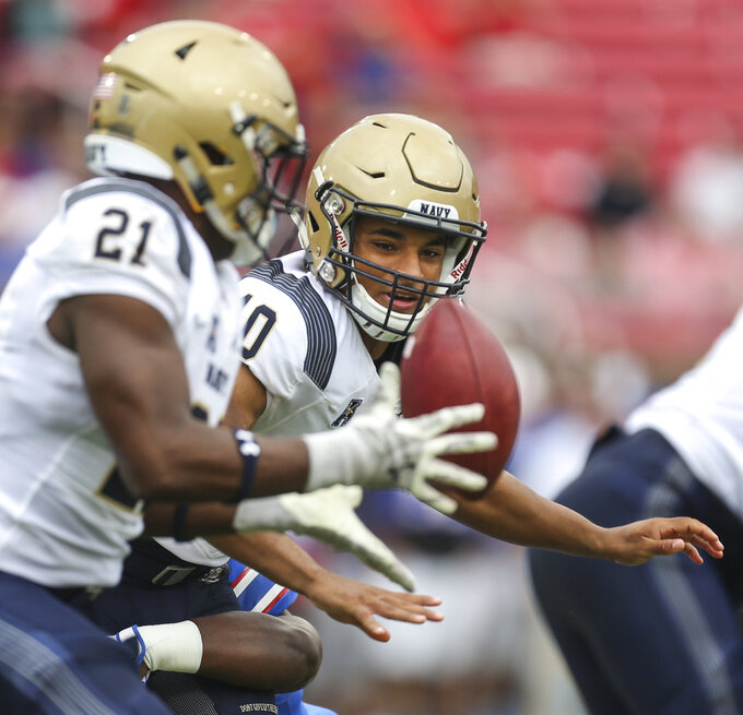 Navy quarterback Malcolm Perry (10) hands off to tight end Tre Walker (21) during the first quarter  of an NCAA college football game against SMU, Saturday, Sept. 22, 2018, at Gerald J. Ford Stadium in Dallas. (Ryan Michalesko/The Dallas Morning News via AP)