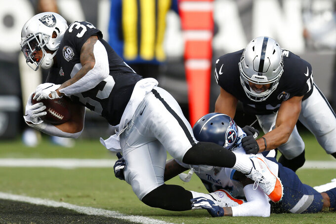 Oakland Raiders running back DeAndre Washington (33) scores a touchdown past Tennessee Titans defensive back Tramaine Brock during the first half of an NFL football game in Oakland, Calif., Sunday, Dec. 8, 2019. (AP Photo/D. Ross Cameron)