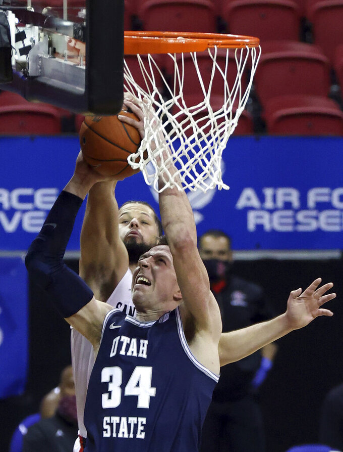 San Diego State guard Jordan Schakel (20) blocks a shot from Utah State forward Justin Bean (34) during the first half of an NCAA college basketball game in the championship of the Mountain West Conference men's tournament Saturday, March 13, 2021, in Las Vegas. (AP Photo/Isaac Brekken)
