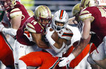 Boston College linebacker Max Richardson (14) tackles Miami running back Travis Homer (24) during the first half of an NCAA college football game in Boston, Friday, Oct. 26, 2018. (AP Photo/Michael Dwyer)