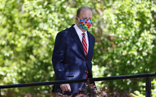 Colorado Gov. Jared Polis wears a face mask as he heads into a news conference on the state's efforts against the spread of the new coronavirus Tuesday, May 26, 2020, in Denver. (AP Photo/David Zalubowski)