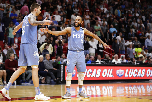 Minnesota Timberwolves guard Jordan McLaughlin (6) and forward Juancho Hernangomez (41) celebrate in the final seconds of the second half of an NBA basketball game against the Miami Heat, Wednesday, Feb. 26, 2020, in Miami. (AP Photo/Wilfredo Lee)