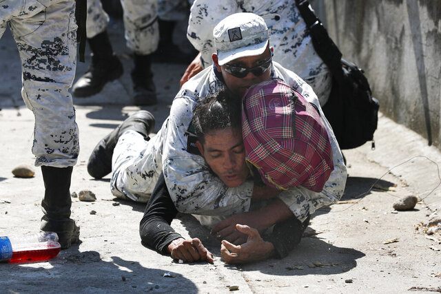 A Mexican National Guard detains a Central American migrant after he crossed the Suchiate River with a group of migrants from Guatemala into Mexico near Ciudad Hidalgo, Mexico, Monday, Jan. 20, 2020. More than a thousand Central American migrants hoping to reach the United States marooned in Guatemala are walking en masse across a river leading to Mexico in an attempt to convince authorities there to allow them passage through the country. (AP Photo/Marco Ugarte)