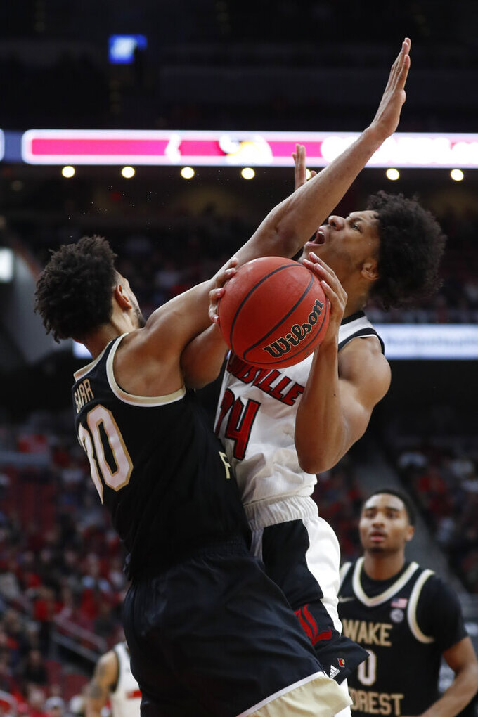 Louisville forward Dwayne Sutton (24) is fouled by Wake Forest center Olivier Sarr (30) during the second half of an NCAA college basketball game Wednesday, Feb. 5, 2020, in Louisville, Ky. Louisville won 86-76. (AP Photo/Wade Payne)