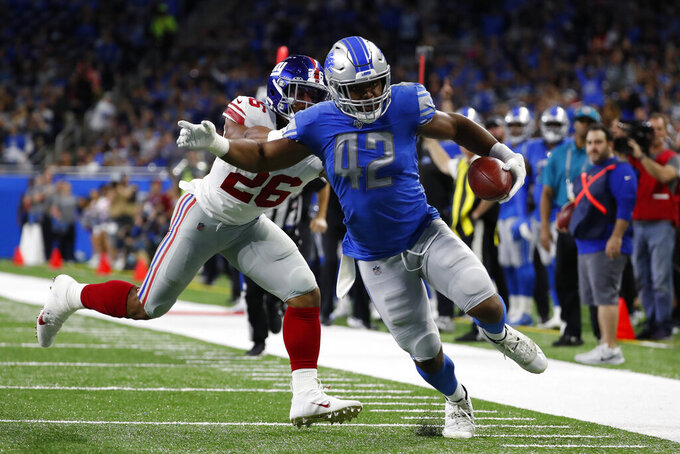 Detroit Lions outside linebacker Devon Kennard (42), chased by New York Giants running back Saquon Barkley (26), picks up a fumble and returns 13-yards for a touchdown during the first half of an NFL football game, Sunday, Oct. 27, 2019, in Detroit. (AP Photo/Rick Osentoski)