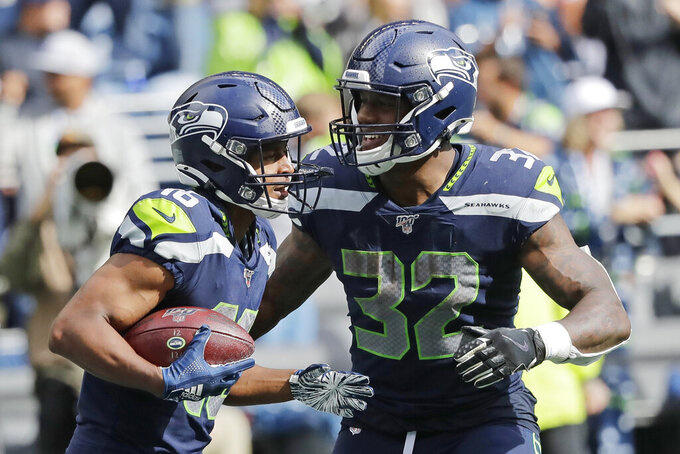 Seattle Seahawks running back Chris Carson (32) celebrates with wide receiver Tyler Lockett, left, after Lockett scored a touchdown against the Cincinnati Bengals during the second half of an NFL football game Sunday, Sept. 8, 2019, in Seattle. (AP Photo/John Froschauer)