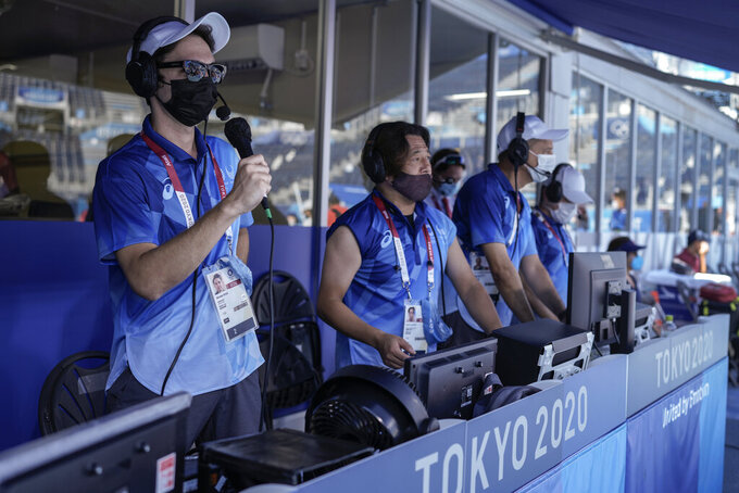 Disc jockey Jeremy Roueche, left, speaks during a men's beach volleyball quarterfinal match at the 2020 Summer Olympics, Thursday, Aug. 5, 2021, Tokyo, Japan. Everyone at the Olympics has had to adjust to the absence of crowds that have stripped the Tokyo Games of their usual flag-waving, anthem-singing spirit. But perhaps no one has faced a bigger challenge than the courtside entertainment at Shiokaze Park. (AP Photo/Petros Giannakouris)