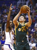 FILE - In this April 3, 2019, file photo, Utah Jazz guard Grayson Allen (24) slips past Phoenix Suns guard Troy Daniels, left, to score during the second half of an NBA basketball game, in Phoenix. A person with knowledge of the decision says the Memphis Grizzlies have traded veteran point guard Mike Conley, who has played the most games in franchise history, to the Utah Jazz. The person says the Grizzlies swapped Conley for Jae Crowder, Kyle Korver and Grayson Allen. The person spoke to The Associated Press Wednesday, June 19, 2019, on condition of anonymity because neither Memphis nor Utah has announced the trade. (AP Photo/Ross D. Franklin, File)