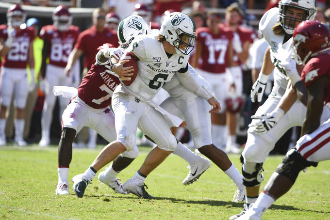 Portland State quarterback Davis Alexander tries to get away from Arkansas defender Joe Foucha as he scrambles out of the pocket in the first half of an NCAA college football game, Saturday, Aug. 31, 2019 in Fayetteville, Ark. (AP Photo/Michael Woods)