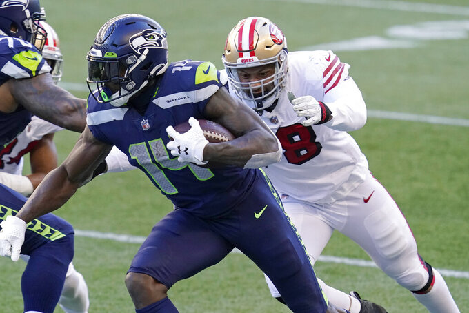 Seattle Seahawks wide receiver DK Metcalf (14) runs as San Francisco 49ers defensive end Jordan Willis, right, closes in during the second half of an NFL football game, Sunday, Nov. 1, 2020, in Seattle. (AP Photo/Elaine Thompson)