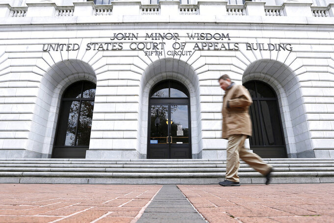 FILE - In this Jan. 7, 2015, file photo, a man walks in front of the 5th U.S. Circuit Court of Appeals in New Orleans. Texas should be allowed to halt a common second-trimester abortion procedure, the state's lawyers told a federal appeals court Thursday, Jan. 21, 2021, in a hearing punctuated by debates over fetal pain and the rights of women to medically safe abortion. (AP Photo/Jonathan Bachman, File)