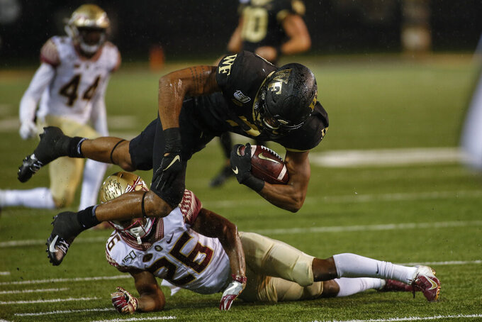 Wake Forest wide receiver Scotty Washington dives over Florida State defensive back Asante Samuel Jr. (26) after a catch in the second half of an NCAA college football game in Winston-Salem, N.C., Saturday, Oct. 19, 2019. Wake Forest won 22-20. (AP Photo/Nell Redmond)