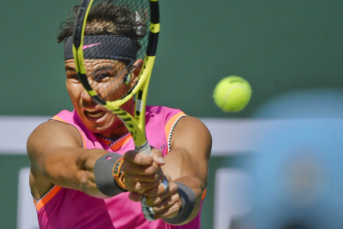 FILE - In this Friday, March 15, 2019 file photo, Spain's Rafael Nadal hits a return to Russia's Karen Khachanov at the BNP Paribas Open tennis tournament, in Indian Wells, Calif. Rafael Nadal is expected to make his return from a knee injury at the Monte Carlo Masters after being included in the official list of players on Thursday, March 21. Nadal has won Monte Carlo a record 11 times and held a 46-match winning streak from 2005-13 - the most consecutive tournament wins by any man or woman. (AP Photo/Mark J. Terrill, file)