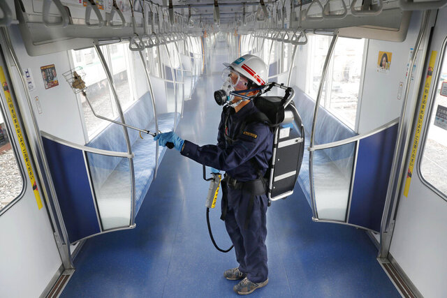 A Tokyo Metro worker, wearing goggle and protective mask, sprays chemicals to make anti-virus coating inside a passenger car at its depot Thursday, July 9, 2020, in Tokyo. The subway company plans to disinfect all 2720 cars by mid August this year, Kyodo News reported.  Japan lifted a seven-week pandemic state emergency in late May, and social and business activity have since largely resumed. (Kyodo News via AP)