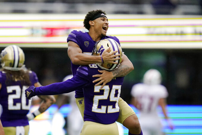 Washington's Trent McDuffie leaps into the arms of Julius Irvin as they celebrate a Washington touchdown against Arkansas State in the second half of an NCAA college football game Saturday, Sept. 18, 2021, in Seattle. (AP Photo/Elaine Thompson)