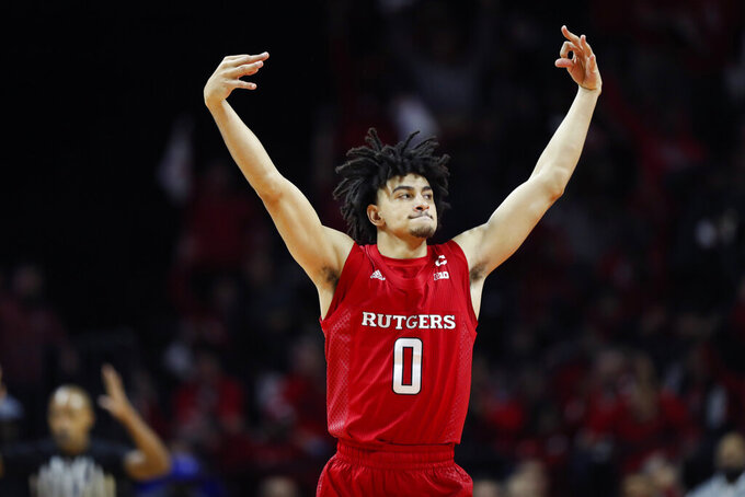 Rutgers guard Geo Baker (0) celebrates after hitting a three-point shot during the first half of an NCAA college basketball game against Seton Hall, Saturday, Dec. 14, 2019, in Piscataway, N.J. (AP Photo/Kathy Willens)