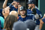 Seattle Mariners' Ty France (23) is congratulated in the dugout after hitting a two-run home run off of Texas Rangers relief pitcher Joe Barlow during the eleventh inning of a baseball game Thursday, Aug. 19, 2021, in Arlington, Texas. Seattle won 9-8. (AP Photo/Jeffrey McWhorter)