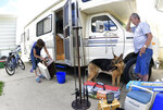 Carol Dworshak cleans a food cooler as Doug watches while they organize and fill their RV with their camping gear and other household items on June 25, 2019 at their Mandan, N.D. home.  (Mike McCleary/The Bismarck Tribune via AP)