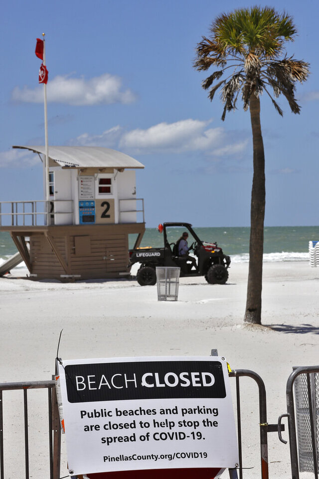FILE - In this Thursday, April 30, 2020 file photo, Lifeguards on Clearwater Beach change shifts on the closed beach in Clearwater Beach, Fla. Memorial Day weekend historically signifies the start of the summer vacation season as families throughout the U.S. plan trips to Florida's beaches and theme parks. But as the state just begins to reopen from two months of quarantining, some officials welcome the boost to the struggling tourism industry while trying to prevent a resurgence of COVID-19. (AP Photo/Chris O'Meara, File)