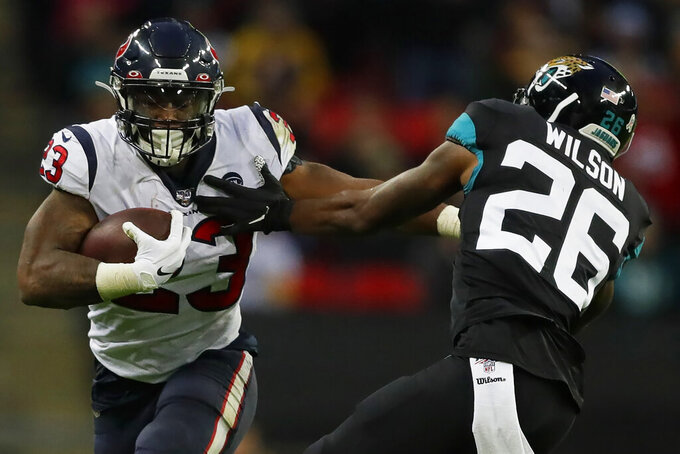 Houston Texans running back Carlos Hyde (23) runs against Jacksonville Jaguars free safety Jarrod Wilson (26) during the second half of an NFL football game at Wembley Stadium, Sunday, Nov. 3, 2019, in London. (AP Photo/Kirsty Wigglesworth)