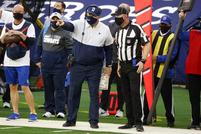 Dallas Cowboys head coach Mike McCarthy, center left, talks with down judge Tripp Sutter, right, in the second half of an NFL football game against the San Francisco 49ers in Arlington, Texas, Sunday, Dec. 20, 2020. (AP Photo/Michael Ainsworth)