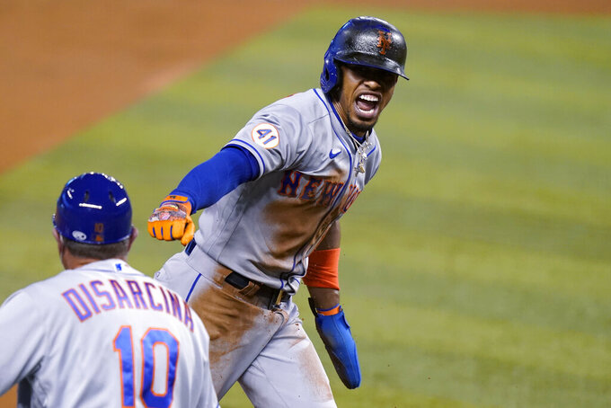 New York Mets' Francisco Lindor runs past third base to score on a throwing error by Miami Marlins center fielder Magneuris Sierra during the first inning of a baseball game, Friday, May 21, 2021, in Miami. (AP Photo/Lynne Sladky)