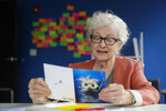 Anne Montgomery, mother of Democratic presidential candidate South Bend Mayor Pete Buttigieg, reads over letters and card written to the campaign in his campaign office in South Bend, Ind., Wednesday, Sept. 25, 2019. (AP Photo/Michael Conroy)