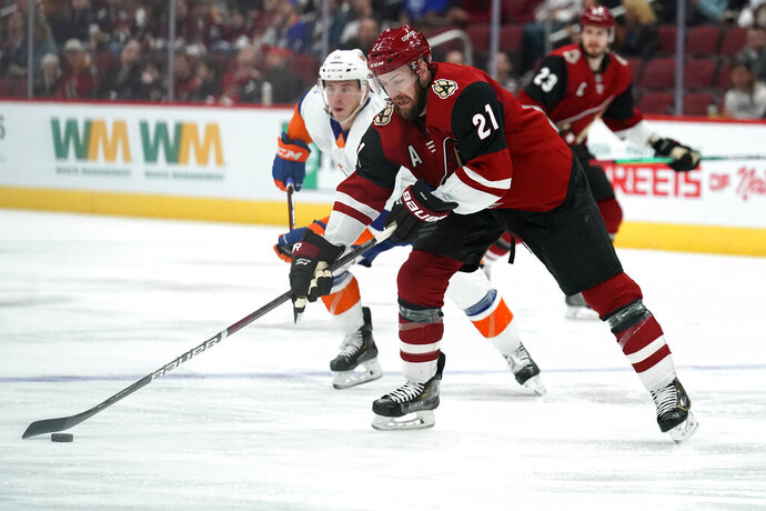 Arizona Coyotes center Derek Stepan (21) skates past New York Islanders left wing Anthony Beauvillier (18) in the second period during an NHL hockey game, Monday, Feb. 17, 2020, in Glendale, Ariz. (AP Photo/Rick Scuteri)