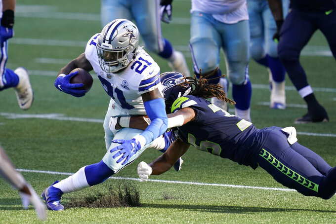 Dallas Cowboys running back Ezekiel Elliott (21) is tackled by Seattle Seahawks cornerback Ryan Neal during the second half of an NFL football game, Sunday, Sept. 27, 2020, in Seattle. (AP Photo/Elaine Thompson)