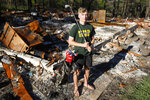 Cade Weins, a senior at Paradise High School, poses with his golf clubs at the burned out ruins of his home in Paradise, Calif., Wednesday, June 5, 2019. When the Camp Fire swept through the area Weins, a member of the school's golf team, saved his golf clubs as he was evacuating. Weins and the rest of the Paradise High School Class of 2019 are graduating Thursday. (AP Photo/Rich Pedroncelli)