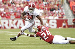 Alabama running back Damien Harris slips past Arkansas defender Jarques McClellion as he runs for a big gain in the first half of an NCAA college football game Saturday, Oct. 6, 2018, in Fayetteville, Ark. (AP Photo/Michael Woods)