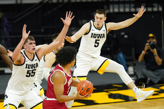 Rutgers guard Ron Harper Jr., center, looks to pass around Iowa center Luka Garza, left, and guard CJ Fredrick, right, during the first half of an NCAA college basketball game, Wednesday, Feb. 10, 2021, in Iowa City, Iowa. (AP Photo/Charlie Neibergall)
