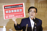 Aichi Gov. Hideaki Ohmura shows off a placard