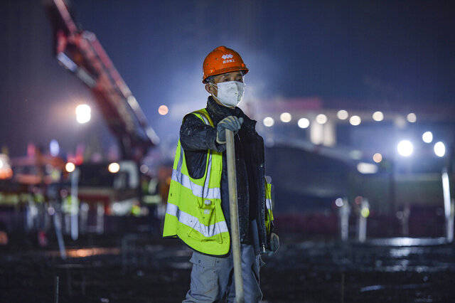 In this Tuesday, Jan. 28, 2020 photo, a construction worker rests at the site of the Huoshenshan temporary field hospital being built in Wuhan in central China's Hubei Province. China as of Wednesday has more infections of a new virus than it did in with SARS, though the death toll is still lower. (Chinatopix via AP)