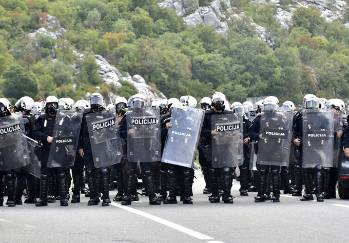 Montenegro riot police guard road near Cetinje, Montenegro, Sunday, Sept. 5, 2021. Riot police used tear gas on protesters who fired gunshots in the air and hurled bottles and stones early Sunday in Montenegro before a planned inauguration of the new head of the Serbian Orthodox Church in the country. The ceremony scheduled in Cetinje, a former capital of the small Balkan nation, has angered opponents of the Serbian church in Montenegro, which declared independence from neighboring Serbia in 2006. (AP Photo/Risto Bozovic)