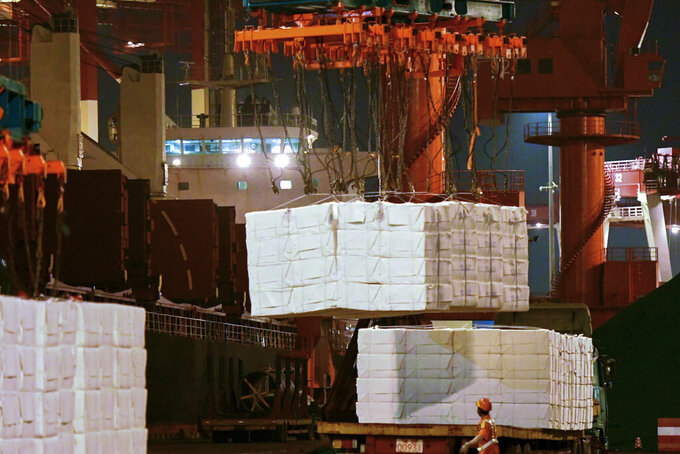 FILE - In this Sept. 25, 2020, file photo, a worker looks at goods being loaded onto a container ship at a dockyard in Qingdao in east China's Shandong province. China's politically sensitive trade surplus with the U.S. soared to a record $75.4 billion November as exports surged 21.1% over a year earlier, propelled by strong demand from American consumers, customs data showed Monday, Dec. 7, 2020. (Chinatopix va AP, File)