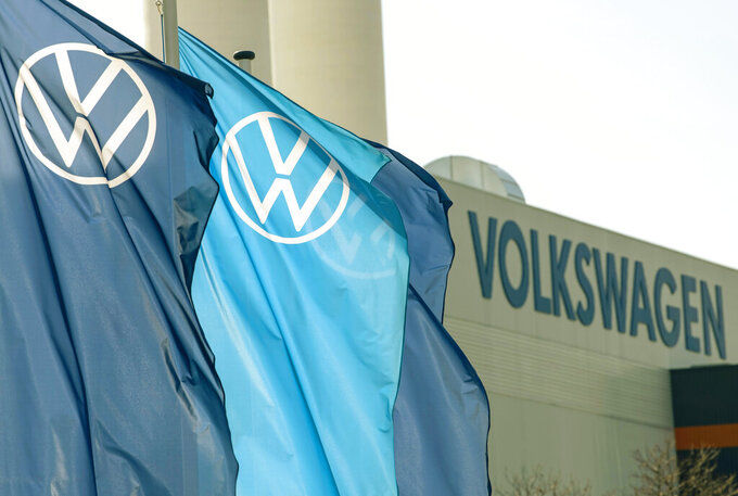 FILE - In this file photo dated Thursday, April 23, 2020, company logo flags wave in front of a Volkswagen factory building in Zwickau, Germany.Luxury brands Audi and Porsche are fattening the bottom line at German automaker Volkswagen. The company's premium brands saw record sales in the first half of the year. That helped the Wolfsburg-based auto giant make more money than it did even before the pandemic. (AP Photo/Jens Meyer, File)