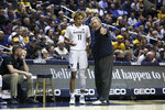 West Virginia coach Bob Huggins speaks with West Virginia forward Emmitt Matthews Jr. (11) after a play during the second half of an NCAA college basketball game Monday, Jan. 20, 2020, in Morgantown, W.Va. (AP Photo/Kathleen Batten)
