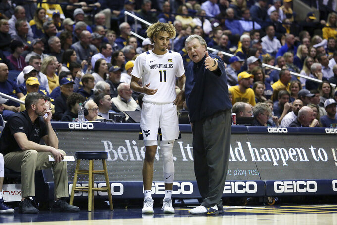 West Virginia coach Bob Huggins speaks with West Virginia forward Emmitt Matthews Jr. (11) after a play during the second half of an NCAA college basketball game Monday, Jan. 20, 2020, in Morgantown, W.Va. (AP Photo/Kathleen Batten)
