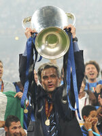 FILE - This is a Saturday, May 22, 2010 file photo of Inter Milan's coach Jose Mourinho as he celebrates with the trophy after the Champions League final soccer match against Bayern Munich at the Santiago Bernabeu stadium in Madrid, Spain. José Mourinho has been hired to coach Italian club Roma starting next season. The move came a few hours after the club's American owners announced that current coach Paulo Fonseca will depart at the end of this season. Mourinho's contract is for three seasons. Mourinho previously coached in Serie A at Inter Milan. (AP Photo/Andres Kudacki, File)