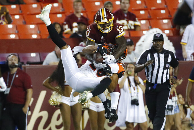 Washington Redskins wide receiver Kelvin Harmon (13) and Cincinnati Bengals defensive back Jordan Brown (26) get tangled up as they both go for a pass during the second half of an NFL preseason football game Thursday, Aug. 15, 2019, in Landover, Md. The Bengals won 23-13. (AP Photo/Alex Brandon)