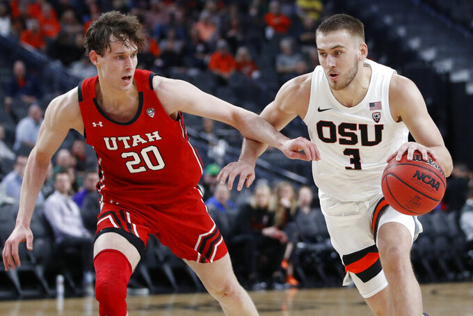 Oregon State's Tres Tinkle (3) drives around Utah's Mikael Jantunen (20) during the first half of an NCAA college basketball game in the first round of the Pac-12 men's tournament Wednesday, March 11, 2020, in Las Vegas. (AP Photo/John Locher)